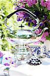 Teekanne und Blumen auf Gartentisch