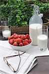 Milk, strawberries, eyeglasses and newspaper on table
