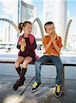 Junge und Mädchen essen Hotdogs, Nathan Philips Square, Toronto, Ontario, Kanada