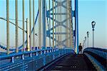 1980s SINGLE MAN PEDESTRIAN ON WALKWAY BENJAMIN FRANKLIN BRIDGE OVER DELAWARE RIVER PHILADELPHIA PENNSYLVANIA USA