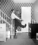 ANNÉES 1950 HOMME TRANSPORTANT DES BOÎTES DE RANGEMENT LE PLANCHER ON STAIRS TRÉBUCHER ET TOMBER SUR TOY