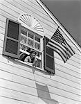 ANNÉES 1930 - ANNÉES 1940 SOURIANT BOY SE PENCHANT SUR LA FENÊTRE À L'ÉTAGE HOLDING DRAPEAU AMÉRICAIN