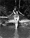 FEMME AUX CHEVEUX LONGS DES ANNÉES 1920 EN VIEUX VÊTEMENTS MAILLOT PERMANENT DANS L'ÉTANG AVEC LES PIEDS DANS L'EAU TOUT À PLONGER EN PLEIN AIR