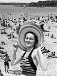 VACANCES DES ANNÉES 1930 MONTAGE PORTRAIT SOURIANT FEMME EN MAILLOT DE BAIN PORTER GRAND CHAPEAU DE PAILLE ET SCÈNE DE PLAGE BONDÉE