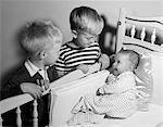 1950s PAIR OF BOYS LOOKING DOWN AT BABY SISTER LYING IN CRIB