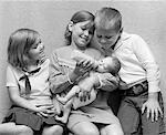 ANNÉES 1970 FILLE BIBERON À BÉBÉ SOEUR AVEC SOEUR & FRÈRE ASSIS SUR CHAQUE CÔTÉ DE SA SUITE À LA RECHERCHE