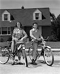 1950ER JAHRE LÄCHELND TEENS AUF SUBURBAN STREET BOY SITZT AUF BIKE-MÄDCHEN STAND NEBEN BIKE MIT KORB