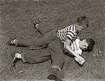 1950ER JAHREN ZWEI JUNGEN TRAGEN T-SHIRTS BLAUE JEANS SPIELEN GROBE KÄMPFEN RINGEN AUF DEM RASEN