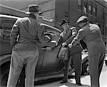 ANNÉES 1940 PAIRE DE GANGSTERS HOLDING HOMME ENTRER DANS LA VOITURE AVEC MALLETTE