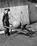 ANNÉES 70 - ANNÉES 80 PERSONNES ÂGÉES FARMER IN SALOPETTES & PAILLE CHAPEAU REGARDANT LA CAMÉRA POUSSANT BROUETTE ANCIENNE AVEC CITROUILLE ÉNORME DESSUS
