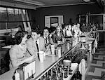 ADOLESCENTS DES ANNÉES 1950, ASSIS AU COMPTOIR DE LA FONTAINE À SODA