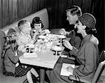 1950s FAMILY OF 5 EATING ICE CREAM IN RESTAURANT