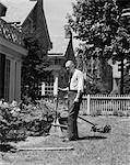 1930s SENIOR MAN STANDING BY GARDEN SHRUBS WITH RAKE PUSH MOWER LAWNMOWER BEHIND HIM