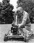 1940s ELDERLY MAN IN YARD KNEELING DOWN TO FIX LAWNMOWER