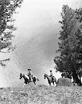 1950s - 1960s TWO MEN ON HORSEBACK RIDING ACROSS FIELD WEARING COWBOY HATS