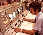 1970s MAN SITTING AT CONTROL PANEL OF NASA MISSION CONTROL HOUSTON  TEXAS USA