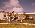 1970s GIRL RIDING BIKE ON SUBURBAN STREET BOY RIDES PIGGY BACK