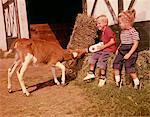 ANNÉES 1950 - ANNÉES 1960 ENFANTS GARÇON ET FILLE ALIMENTATION VEAU BOUTEILLE DE LAIT À L'EXTÉRIEUR DE LA GRANGE