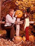 1960s MAN FATHER AND GIRL DAUGHTER  CARVING  HALLOWEEN JACK-O-LANTERN PUMPKIN