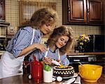 1970s MOTHER DAUGHTER DRESSED ALIKE DECORATING CAKE