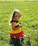 1980s BLONDE GIRL KNEELING IN GRASS HOLDING A DANDELION