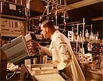 1960s SCIENTIST LAB TECHNICIAN LOOKING INTO OSCILLOSCOPE IN LABORATORY