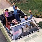 ANNÉES 1970 AFRO-AMÉRICAINE FAMILLE PÈRE MÈRE FILS FILLE AGITANT DE DÉCAPOTABLES EN PLEIN AIR
