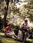 ANNÉES 1970 - ANNÉES 1980 DEUX JEUNES GARÇONS JOUANT DES GUITARES ÉLECTRIQUES, ASSIS À L'EXTÉRIEUR AVEC AMPLIFICATEUR ET GUITARE
