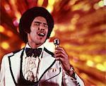 1970s AFRICAN-AMERICAN MAN SINGER WHITE TUXEDO RUFFLED SHIRT SINGING INTO MICROPHONE