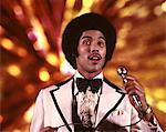 ARTISTE HOMME AFRO-AMÉRICAIN DES ANNÉES 1970 EN CHANT DE SMOKING EN FOND OR MICRO LAMPES