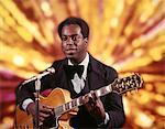 ANNÉES 1970 AFRO-AMÉRICAIN HOMME ARTISTE CHANTEUSE MUSICIENNE PORTANT TUXEDO PLAYING GUITAR CHANTE EN ARRIÈRE-PLAN LUMIÈRES MICROPHONE OR