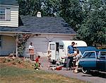 ANNÉES 1960 FAMILLE PÈRE MÈRE FILS DE CHARGEMENT DE LA VOITURE ET LA REMORQUE POUR LES VACANCES D'ÉTÉ EN PLEIN AIR