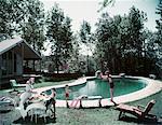 1950s FAMILY MAN WOMAN SON DAUGHTER BACKYARD KIDNEY SHAPE SWIMMING POOL PICNIC FOOD BEACH BALL HOUSE TREES SUMMER