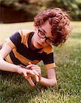 1960s - 1970s GEEKY BOY WEARING STRIPED T-SHIRT BIG EYE GLASSES LYING IN BACKYARD GRASS PLAYING WITH PET REPTILE LIZARD