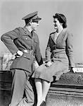 1940s HAPPY COUPLE MAN WEARING ARMY UNIFORM WOMAN SITTING ON STONE WALL