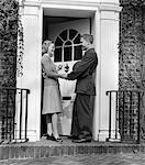 1940s WOMAN GREETING MAN IN SOLDIERS UNIFORM AT FRONT DOOR
