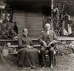 1890s - 1900s PORTRAIT SENIOR COUPLE SEATED IN GARDEN MAN HOLDING EAR TRUMPET