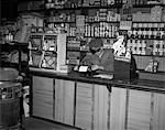 1930s MAN BEHIND COUNTER IN GENERAL STORE USING TYPEWRITER