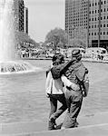 1970ER JAHRE ROMANTISCHE JUNGEN HIPPIE PAAR GEHEN ARM IN ARM NEBEN BRUNNEN
