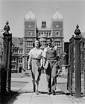 1940s COLLEGE AGED STUDENT COUPLE WALKING THROUGH CAMPUS GATES UNIVERSITY OF PENNSYLVANIA