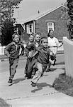 1950s GROUP OF SCHOOL CHILDREN RUNNING AROUND CORNER OF PICKET FENCE IN SUBURBAN NEIGHBORHOOD