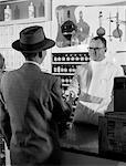 1950s PHARMACIST GIVING PRESCRIPTION TO MAN CUSTOMER