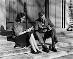 ANNÉES 1940 JEUNE COUPLE ASSIS SUR LES MARCHES AVEC LES MANUELS ET DOCUMENTS DE SOURIRE EN PLEIN AIR