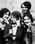 1920ER JAHRE GRUPPE VON VIER FRAUEN VERSAMMELTEN SICH UM CANDLESTICK-TELEFON