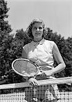 1950s PORTRAIT WOMAN HOLDING TENNIS RACQUET STANDING BEHIND NET OUTDOOR