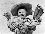 ANNÉES 1940 SOURIANT BOY IN HOLDING AGRICULTEUR CHAPEAU PAILLE TURQUIE IN ARMS REGARDANT LA CAMÉRA
