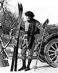 ANNÉES 1920 FEMME AU FOULARD CHAPEAU ET BOTTES DEBOUT DEVANT LA VOITURE TENANT DES SKIS DE BOIS ET DE BAMBOU BÂTONS DE SKI