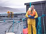 Worker using clipboard at fish farm