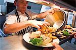 Chef mit Teller in der Küche