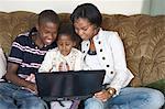 Siblings enjoy playing on a laptop together, Nairobi, Kenya